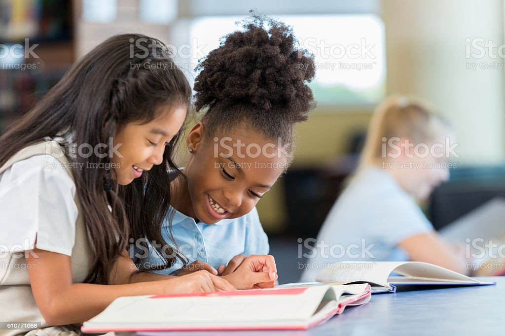 Smiling and cheerful schoolgirls reading a book together at school stock photo