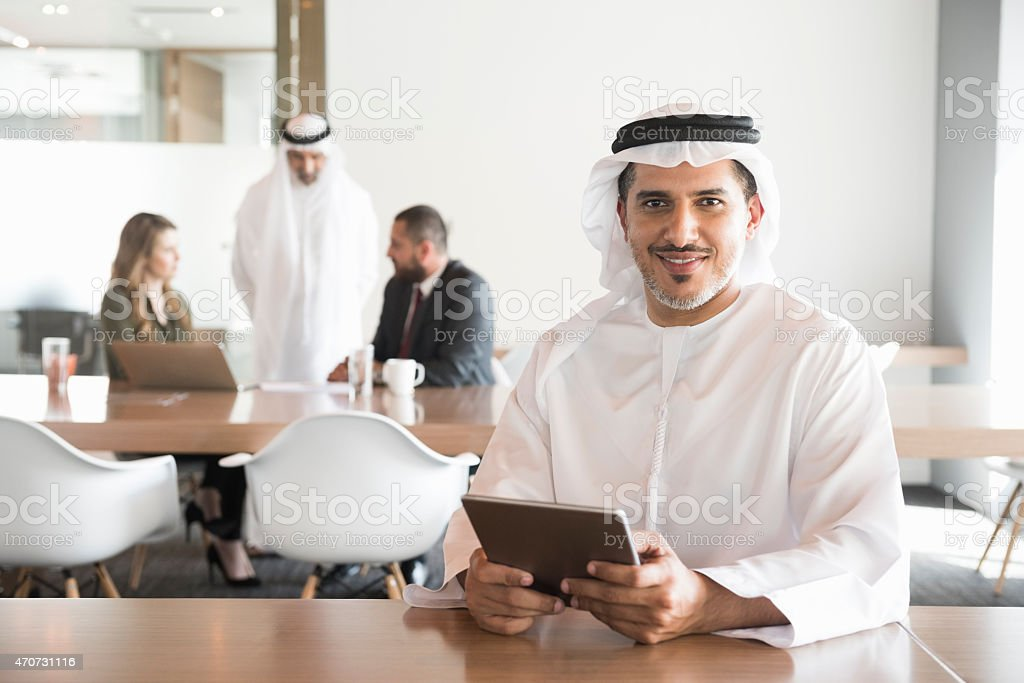 Smiling Arab businessman holding digital tablet in office stock photo
