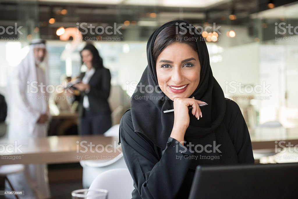 Smiling Arab businesswoman holding pen in office stock photo