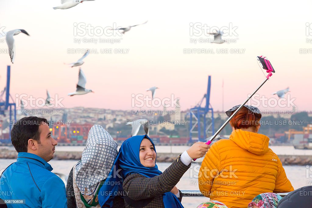 Smiling Arabic Ladies taking self Portrait with Sea Gulls stock photo