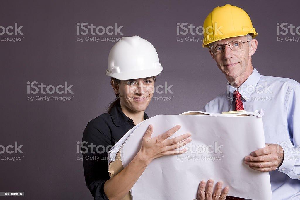 Smiling architects holding blueprints royalty-free stock photo