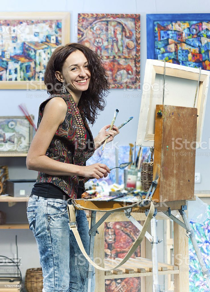 Smiling artist painting in her studio royalty-free stock photo