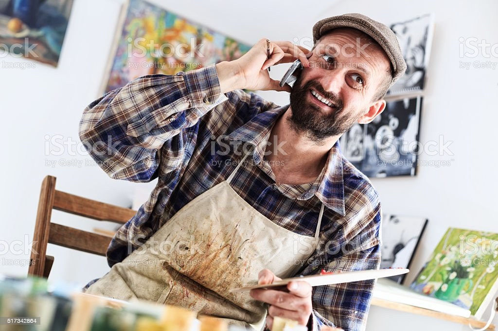 Smiling artist using telephone in his workshop stock photo