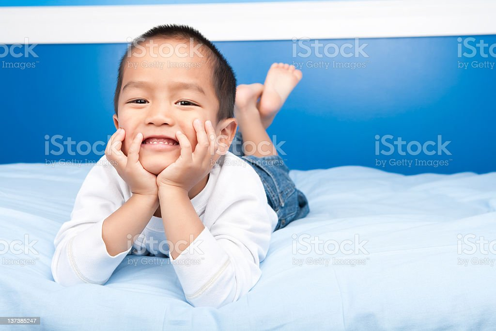 Smiling asian boy laying in bed royalty-free stock photo