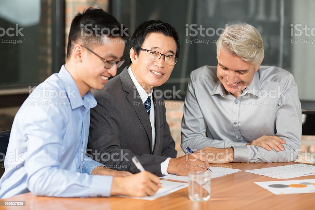 Smiling Asian business people closing deal stock photo
