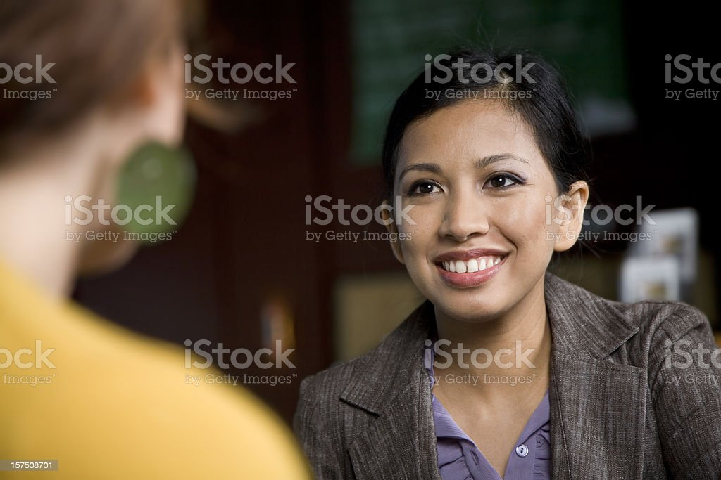 Smiling Asian Business Woman Talking to Her Associate stock photo