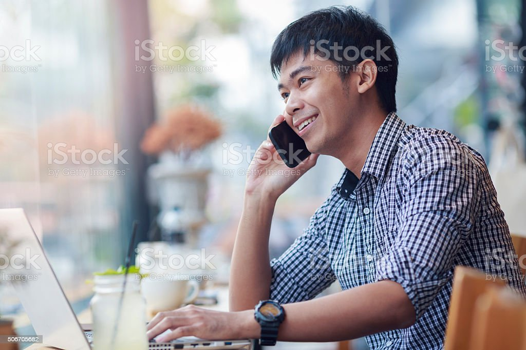 Smiling asian businessman making a call during relax with notebo stock photo
