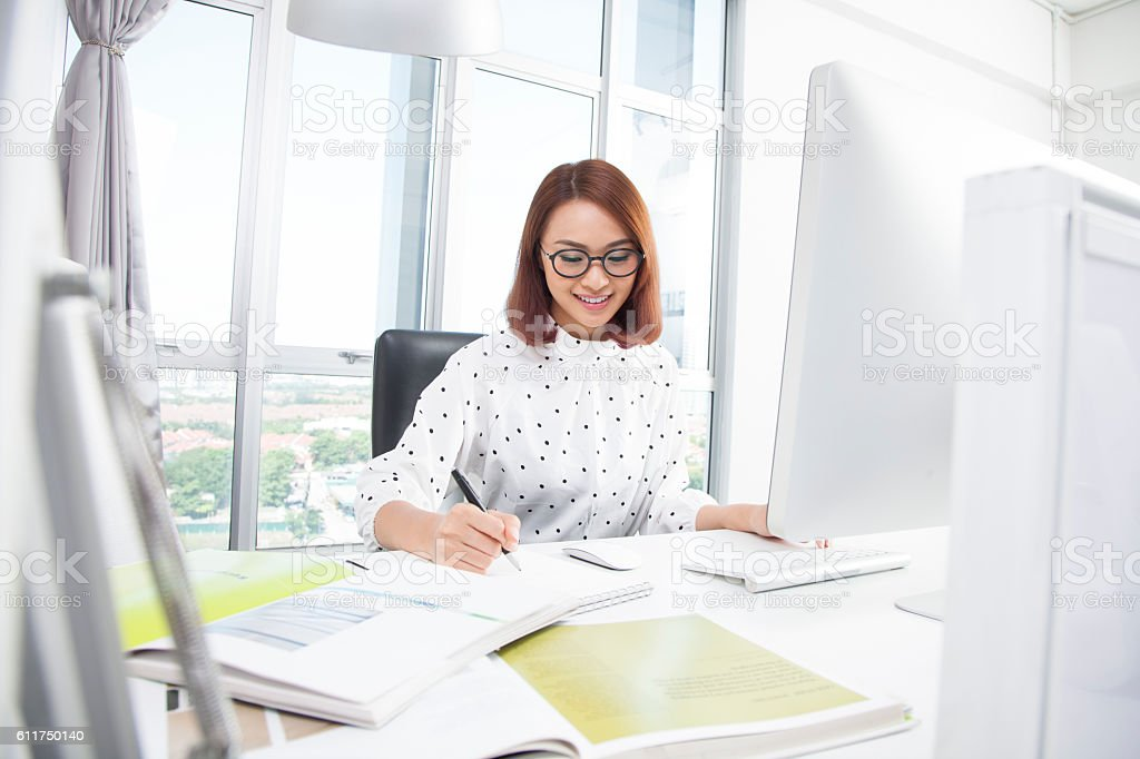 Smiling asian businesswoman at office desk writing stock photo