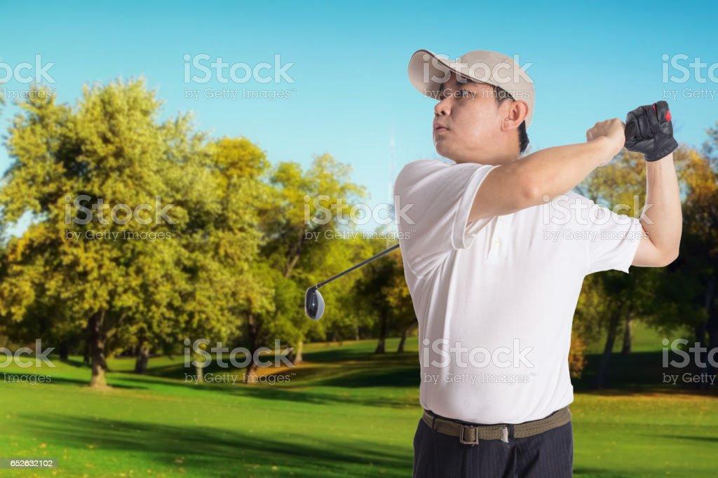 Smiling Asian Chinese Man Swinging Golf Club stock photo