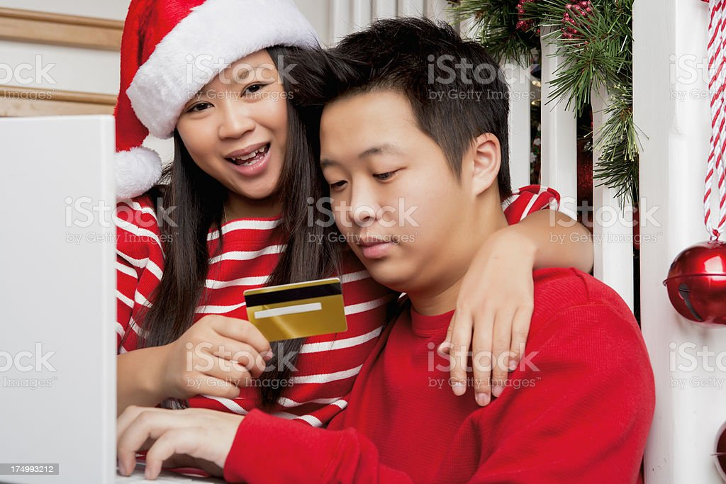 Smiling asian couple christmas online shopping royalty-free stock photo