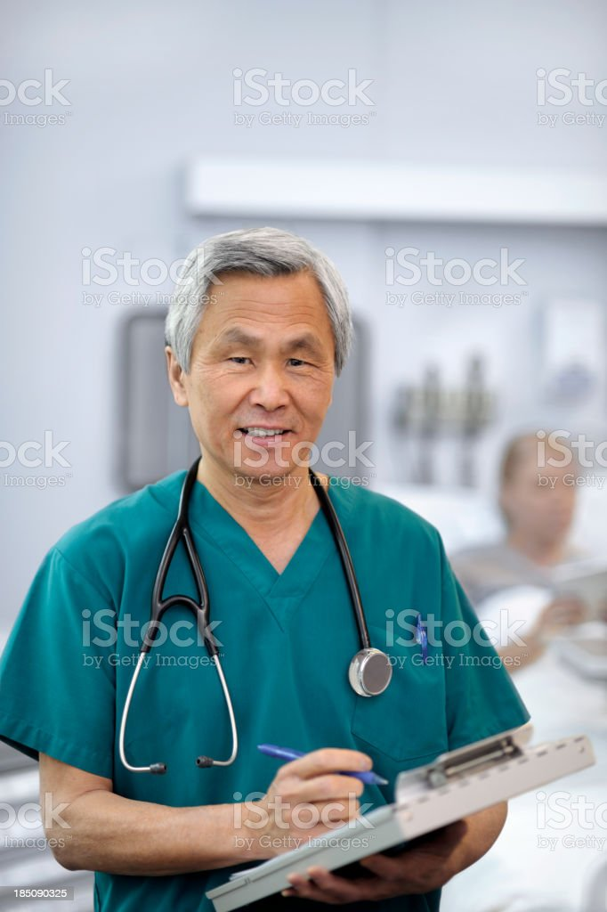 Smiling Asian Doctor Examining Female Patient royalty-free stock photo
