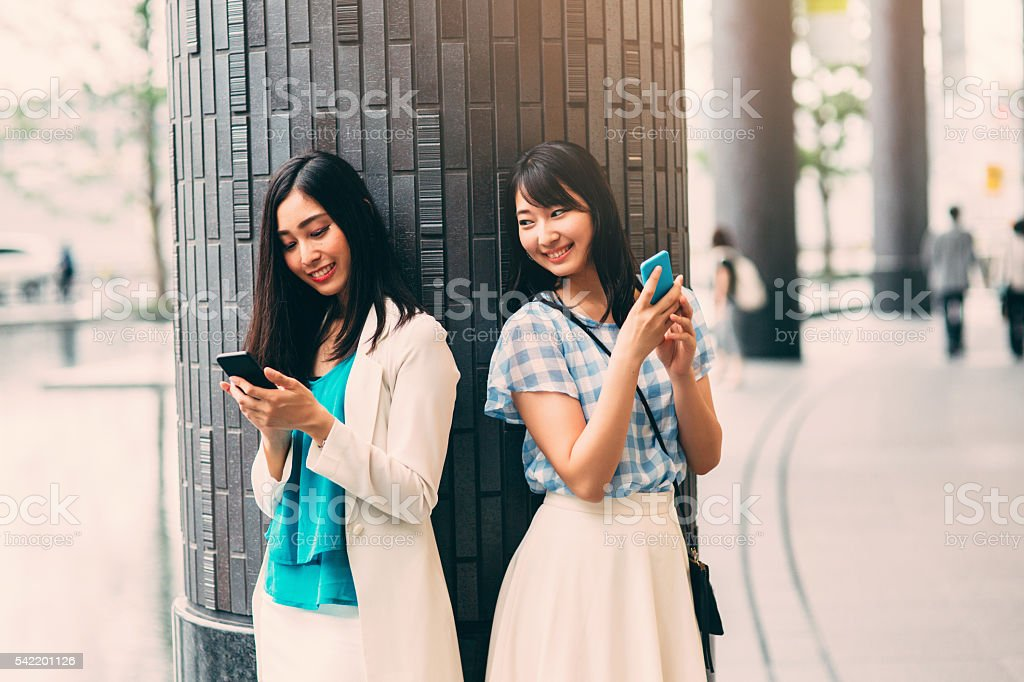 Smiling Asian Ethnicity girls texting stock photo
