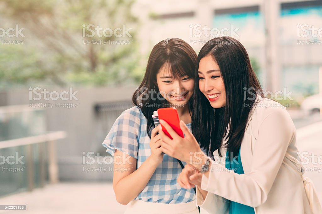 Smiling Asian Ethnicity girls with smart phone