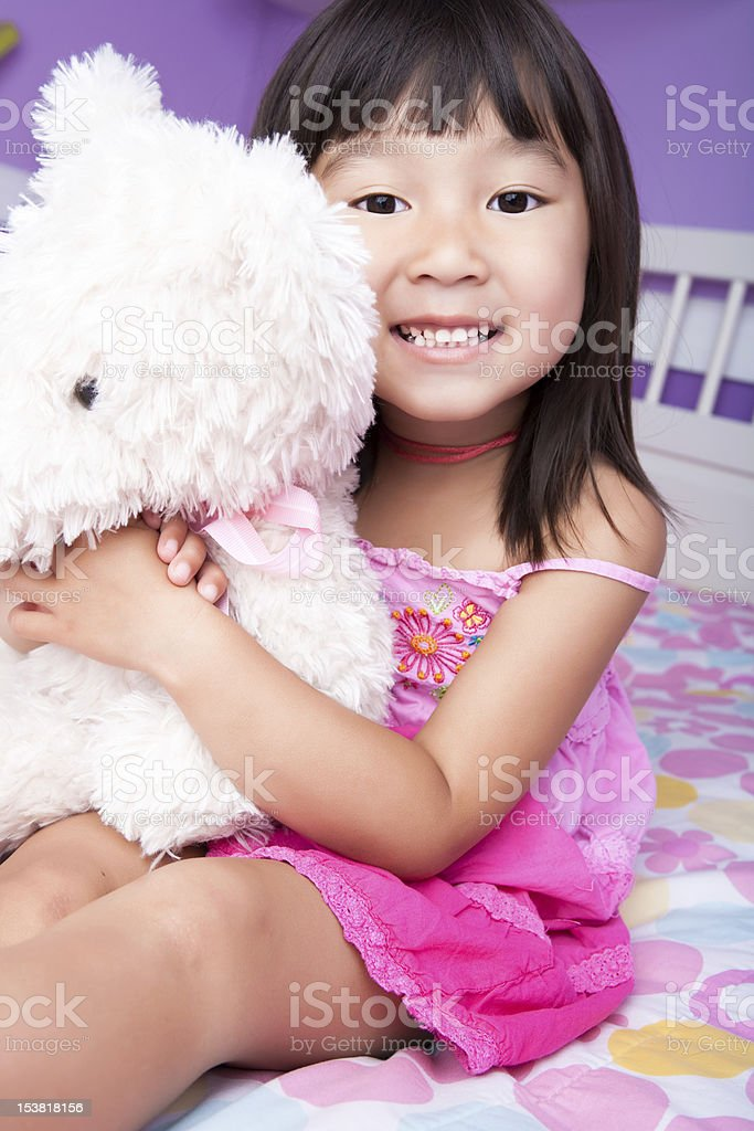 Smiling asian girl hugging teddy bear in bed royalty-free stock photo