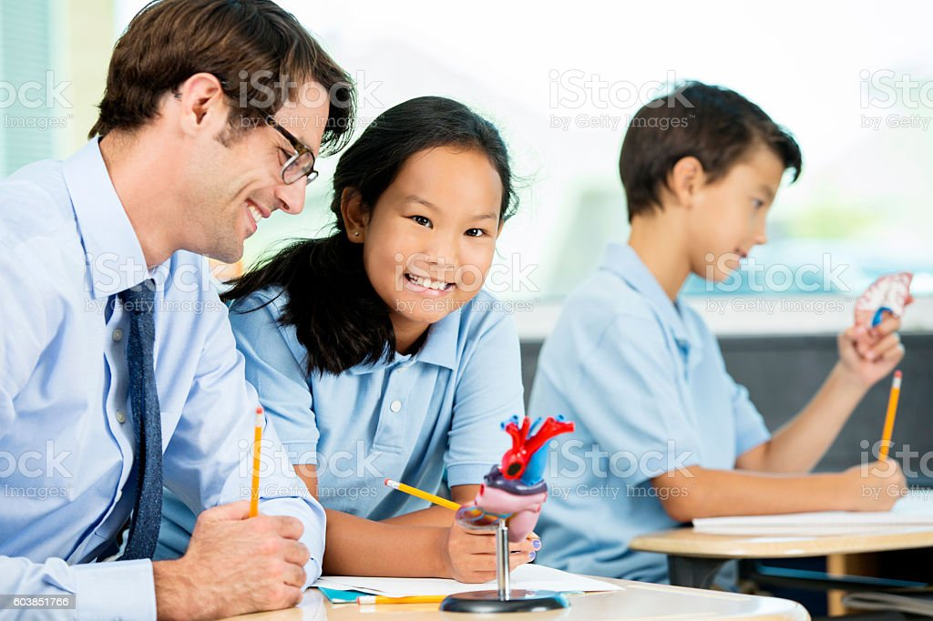 Smiling Asian student with teacher in biology class stock photo