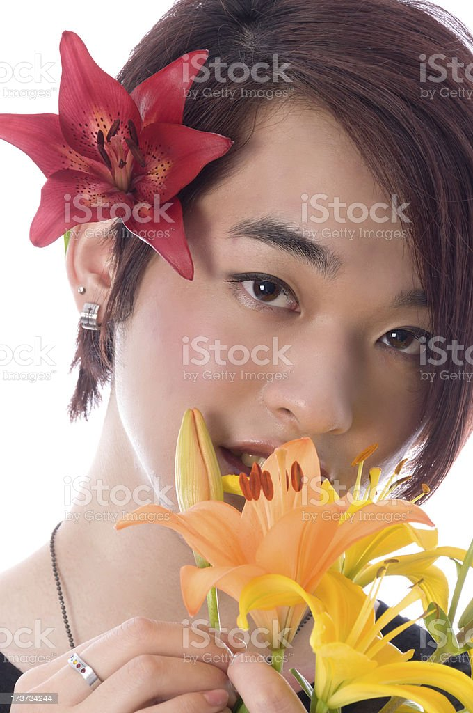 Smiling Asian teen looking over lily bouquet. royalty-free stock photo