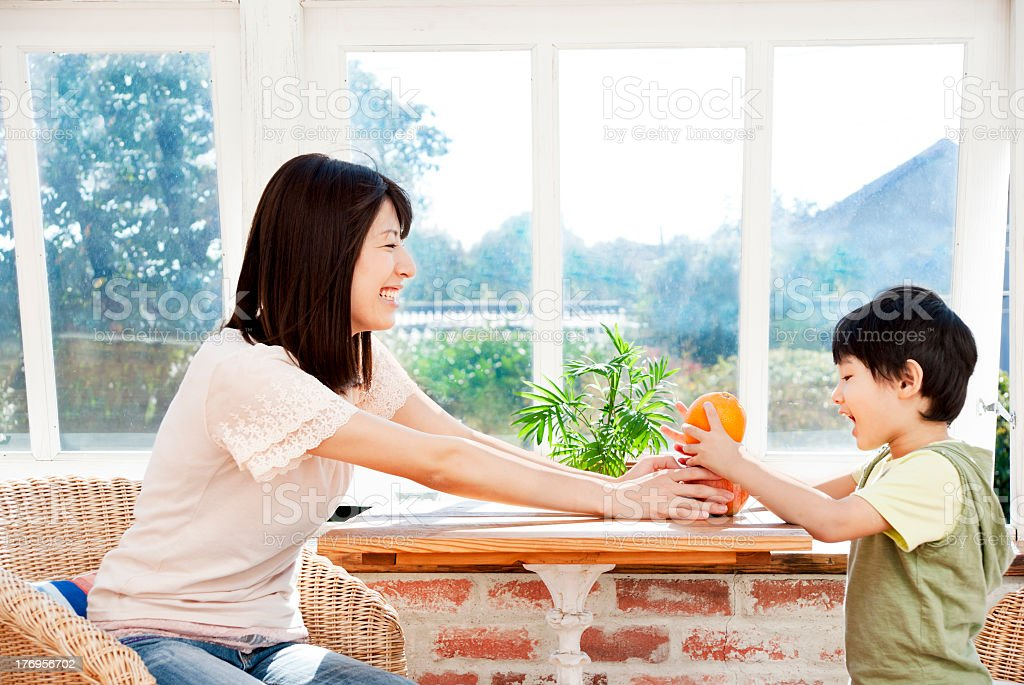Smiling Asian woman handing fruit to smiling Asian boy stock photo