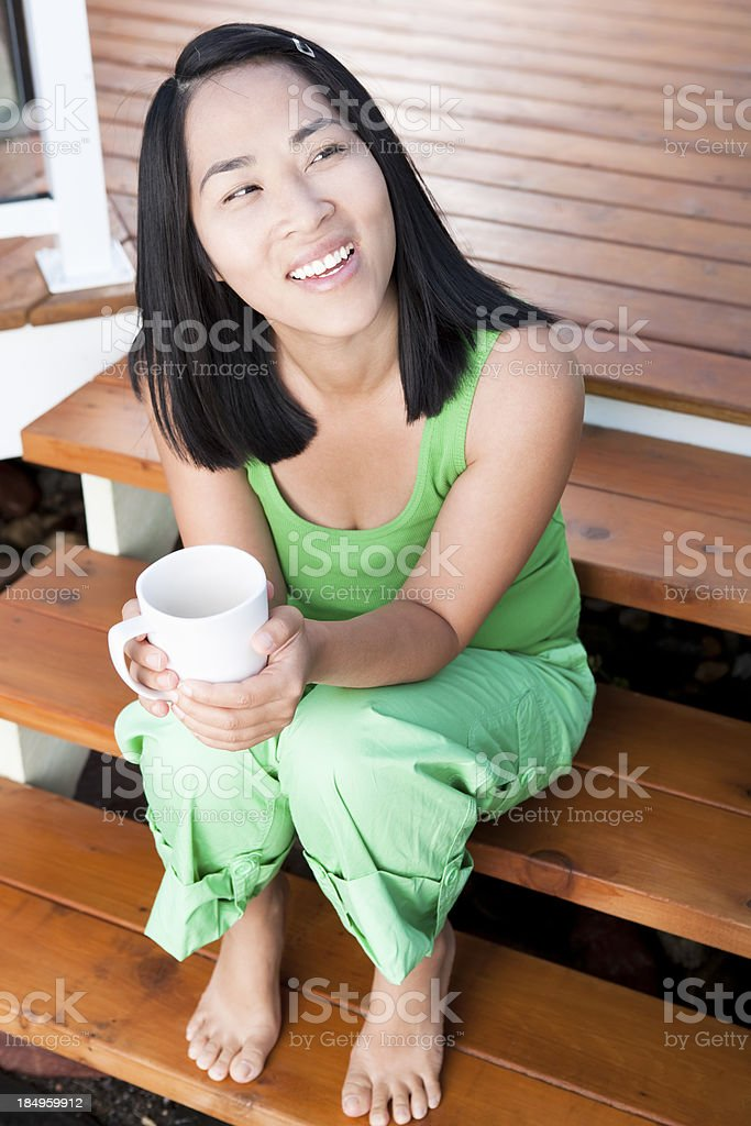 Smiling asian woman holding cup of coffee outdoor royalty-free stock photo