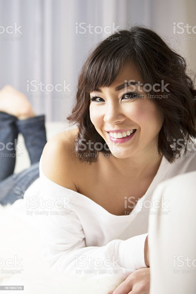 Smiling asian woman laying on couch royalty-free stock photo