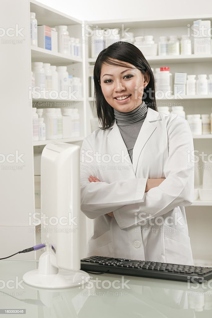 Smiling Asian Woman Pharmacist in a Retail Drug Store Pharmacy royalty-free stock photo