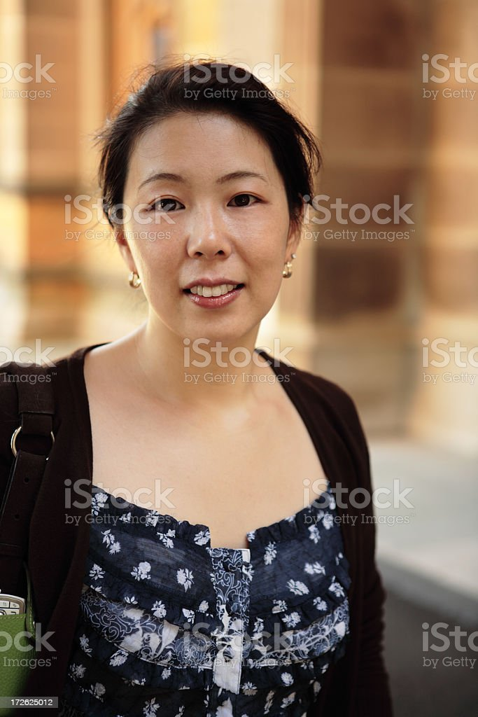Smiling Asian Woman photographed against a brick building stock photo