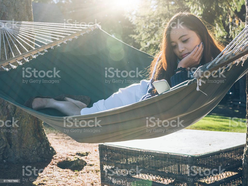 smiling asian woman relaxing on hammock with mobile phone stock photo