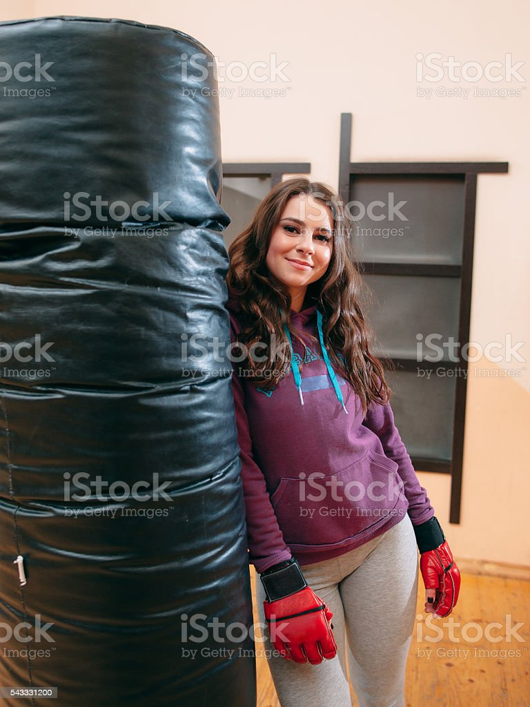 Smiling athletic girl standing near punching bag stock photo