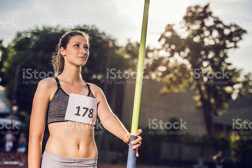 Smiling athletic woman preparing to throw a javelin. stock photo