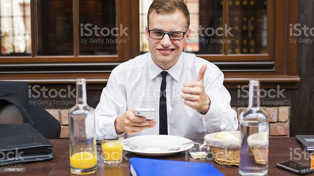 Smiling attractive Businessman sitting with smartphone in restaurant. royalty-free stock photo