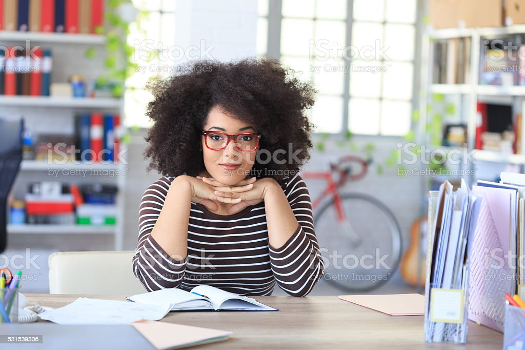 Smiling attractive bussinesswoman sitting on desk at workplace stock photo