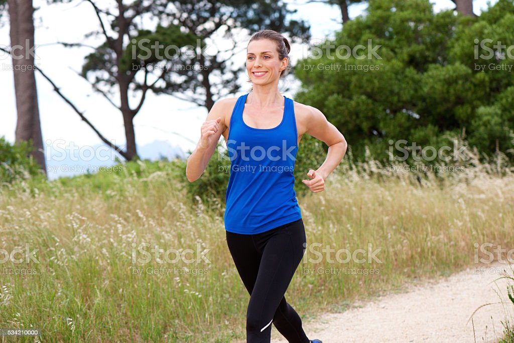 Smiling attractive woman speed walking stock photo