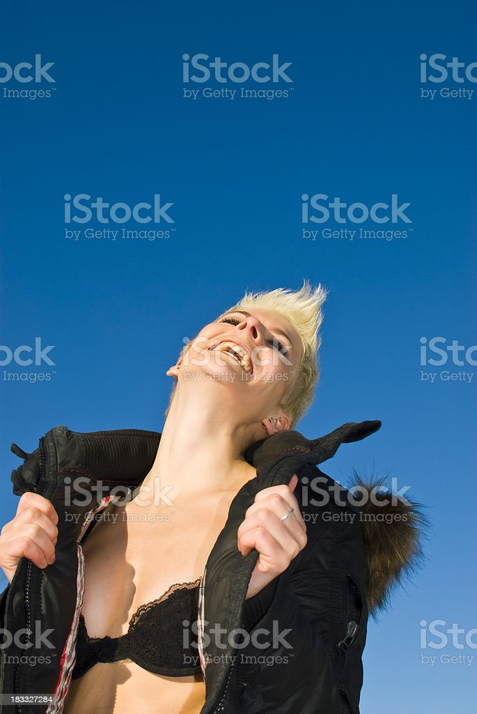 Smiling attractive woman with short blond hair opens her jacket royalty-free stock photo