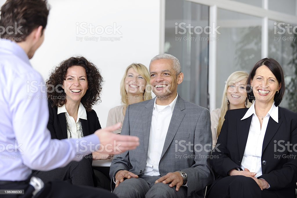 A smiling audience listening to a presentation royalty-free stock photo