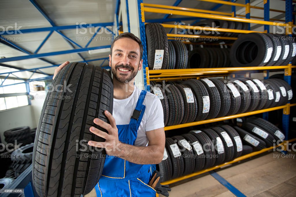 smiling auto mechanic carrying tire stock photo