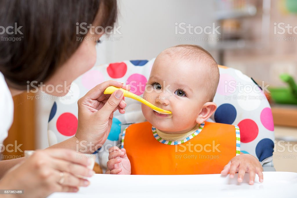 smiling baby eating food with mom on kitchen stock photo