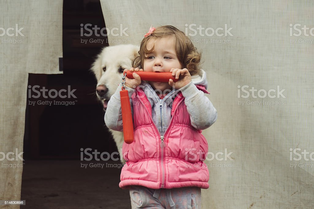 Smiling baby girl holding a red plastic nunchaku stock photo
