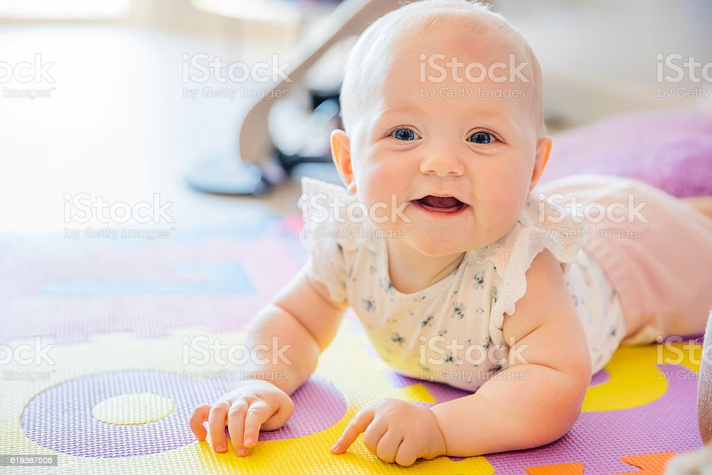 Smiling baby girl with blue eyes playing on floor mate stock photo