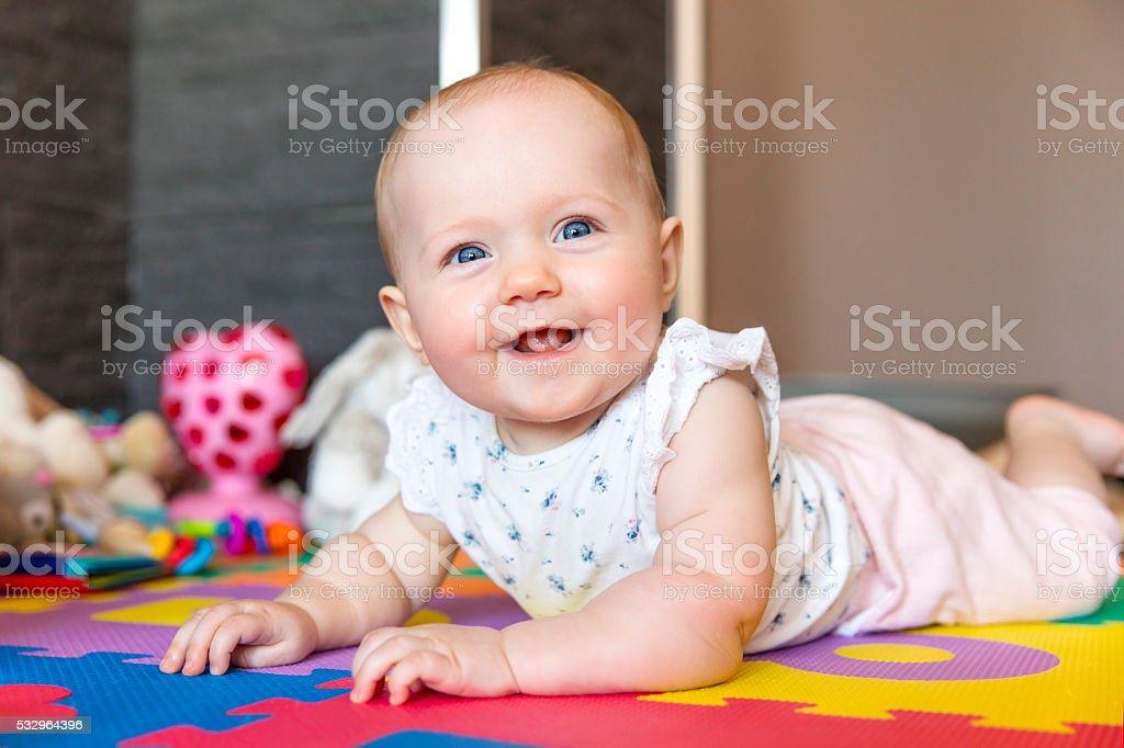 Smiling baby girl with blue eyes playing on floor stock photo
