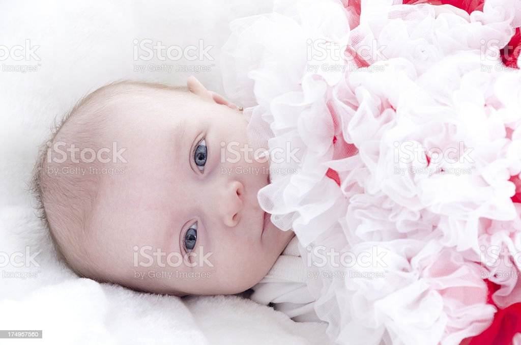 Smiling baby girl with red tutu covering chin. royalty-free stock photo