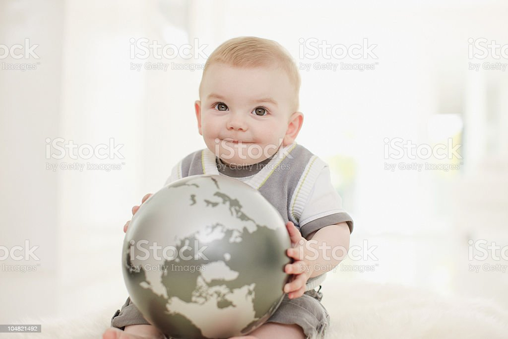 Smiling baby holding globe on floor royalty-free stock photo