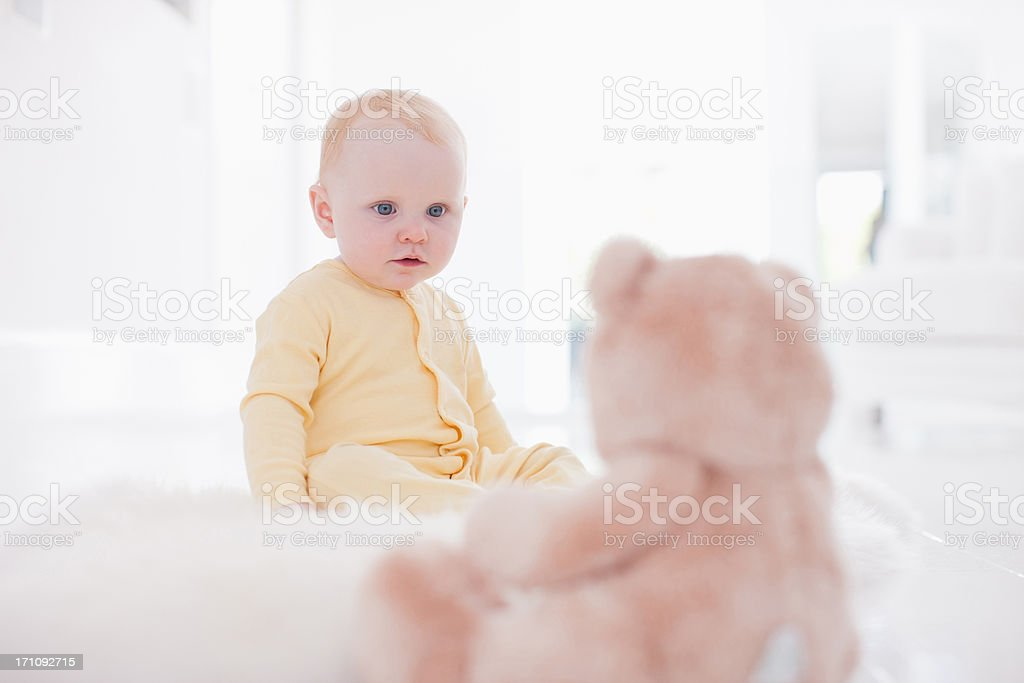 Smiling baby looking at teddy bear on rug stock photo
