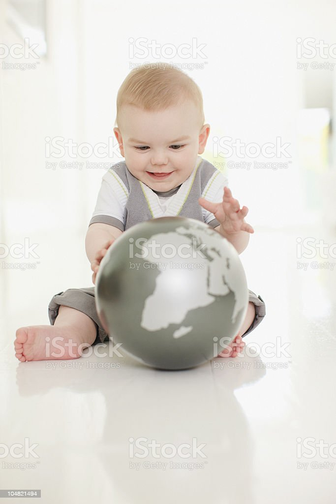 Smiling baby playing with globe on floor royalty-free stock photo