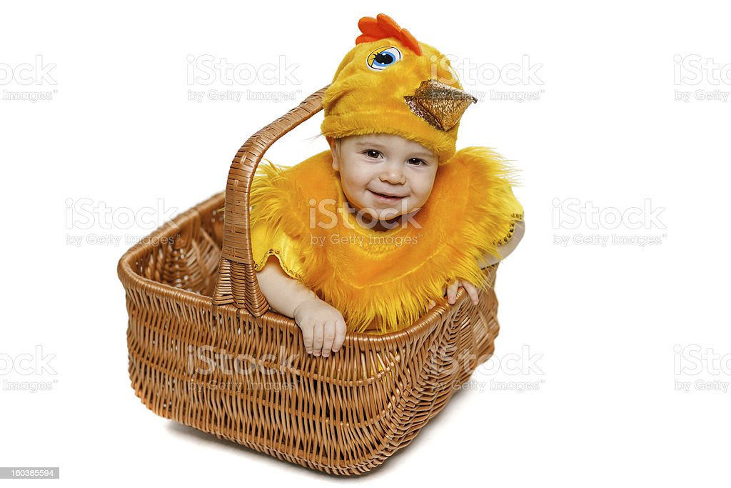 Smiling baby wearing chicken costume sitting in basket stock photo