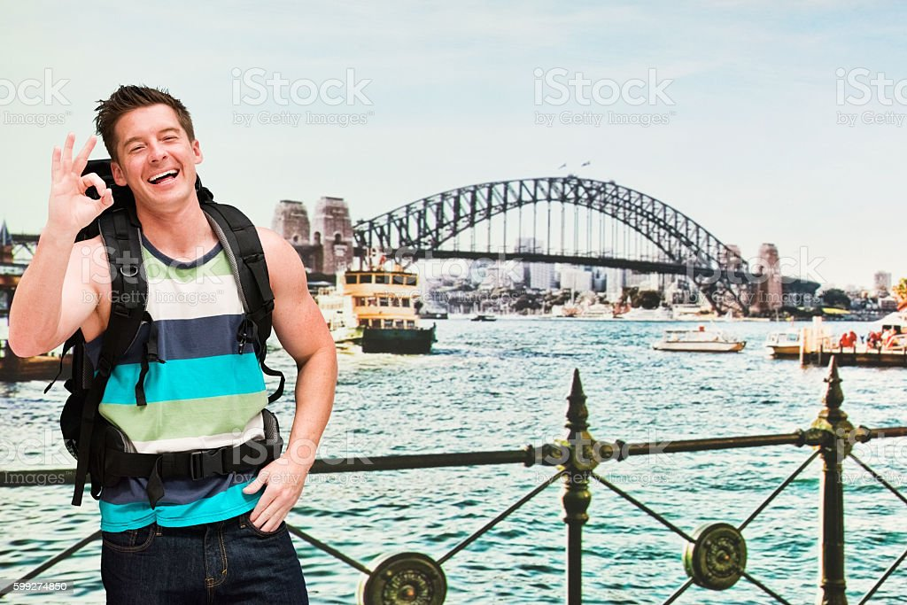 Smiling backpacker giving ok sign stock photo