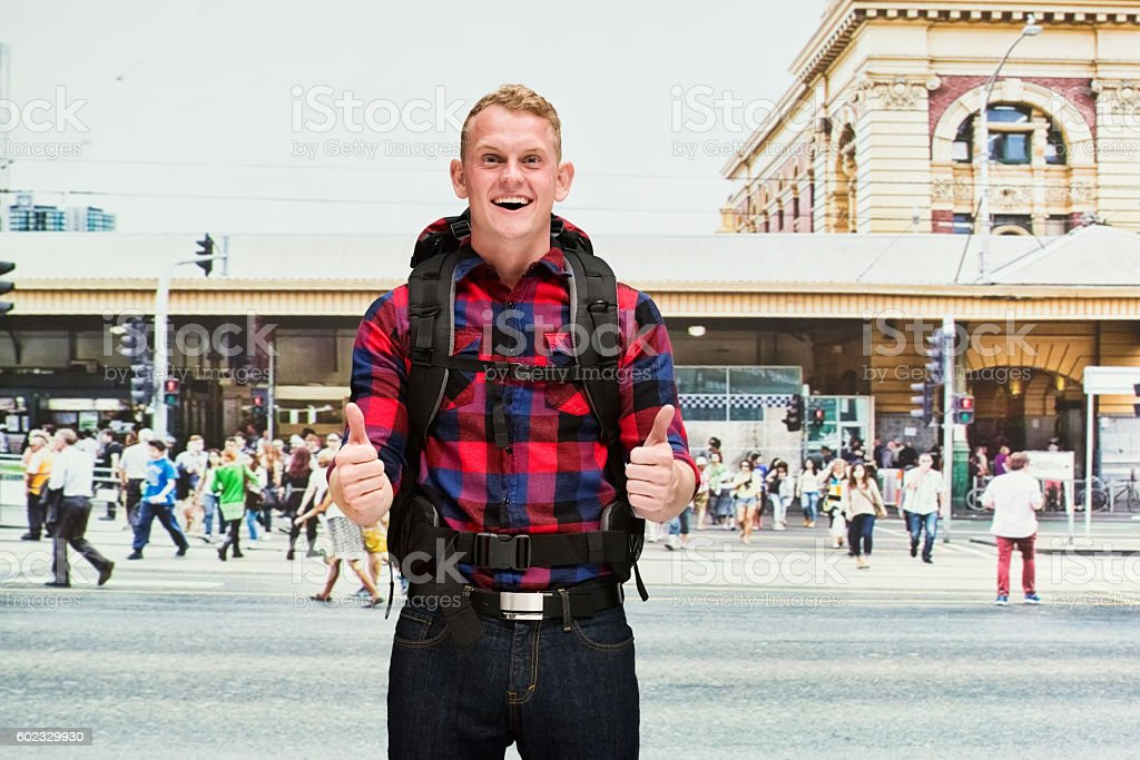 Smiling backpacker giving thumbs up outdoors stock photo