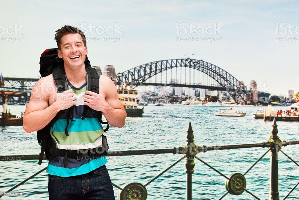 Smiling backpacker in front of harbor bridge stock photo