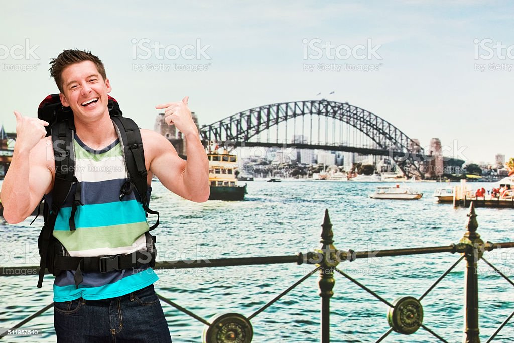 Smiling backpacker pointing at him outdoors stock photo