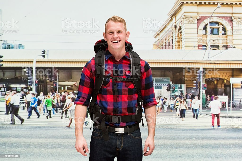 Smiling backpacker standing outdoors stock photo