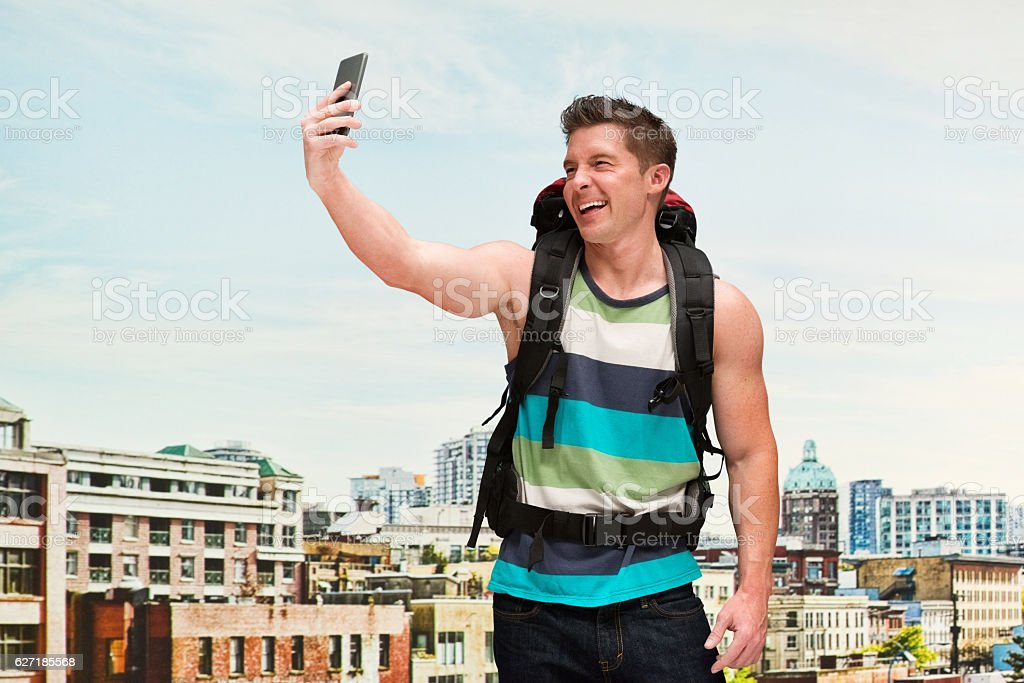 Smiling backpacker taking a selfie outdoors stock photo