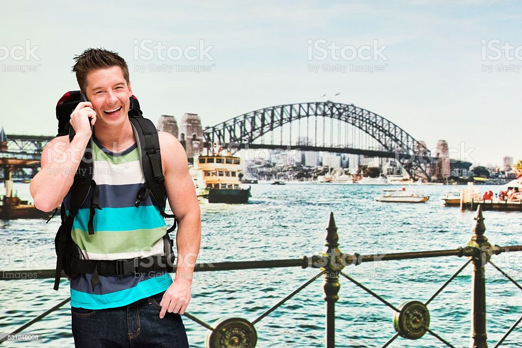 Smiling backpacker talking on phone outdoors stock photo